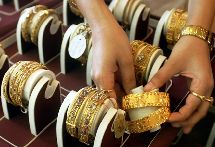 A shopkeeper arranges gold ornaments at a shop in Jammu.