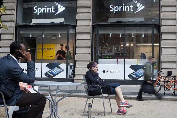 People talk on their mobile phones as passers-by walk past a Sprint store in New York.