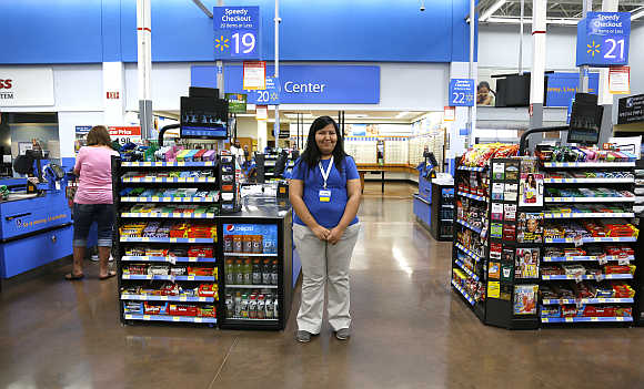 A cashier waits for customers at a Walmart Supercenter in Rogers, Arkansas.
