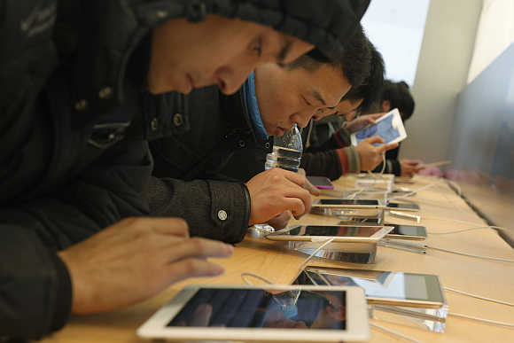 Customers test out iPads in an Apple Store in downtown Shanghai, China.