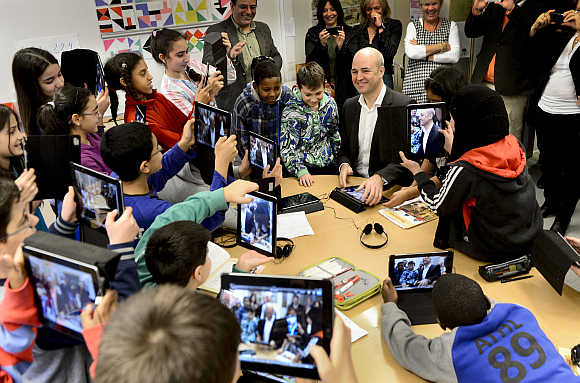 Fifth graders use their iPads to take photos of Sweden's Prime Minister Fredrik Reinfeldt during his visit to Husby School, west of Stockholm.
