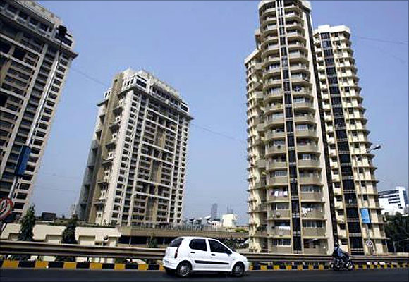 A vehicle drives past residential buildings in India's financial capital Mumbai.