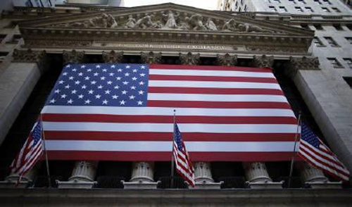 U.S. flags hang on the facade of the New York Stock Exchange.