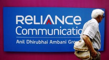 Image: A man walks past a logo of Reliance Communication before the Annual General Meeting in Mumbai.