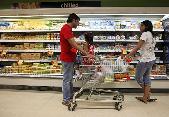 People shop in the chilled foods section of a supermarket.
