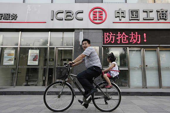 A man cycles a bike carrying his daughter past a branch of Industrial and Commercial Bank of China in Beijing.