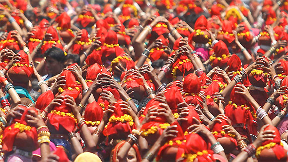 Women carry Kalash, earthen pots containing sacred water with a coconut on top, during a religious procession locally known as Ganga Kalash Yatra in Ahmedabad.