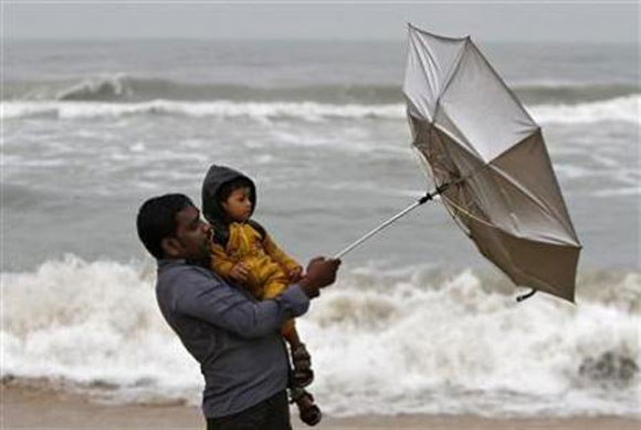 A man carrying his child tries to hold an umbrella at Marina beach in Chennai.