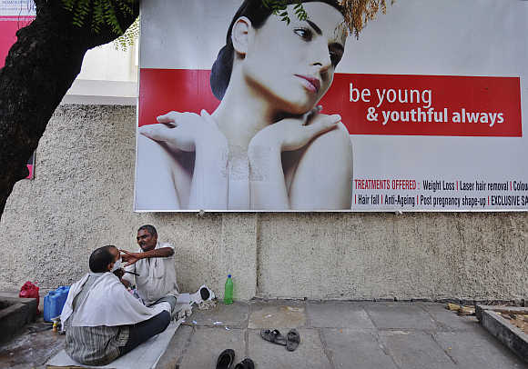 A man receives a shave from a street side barber in front of an advertisement for beauty treatments in Hyderabad.