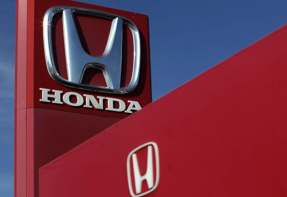 The Honda logo is seen on the forecourt of a car dealer.