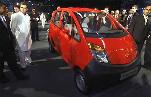 A file photo of Rahul Gandhi (L in white) next to a Tata Nano after its launch at the 9th Auto Expo in New Delhi on January 10, 2008.
