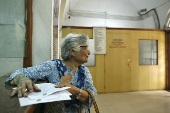 Bulbul Tiwari, 73, writes a telegram to her grandchildren inside the Central Telegraph Office in New Delhi July 10, 2013.