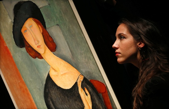 A worker poses with 'Jeanne Hebuterne (au chapeau)' from 1919 by Amedeo Modigliani, at Christie's auction house in London.