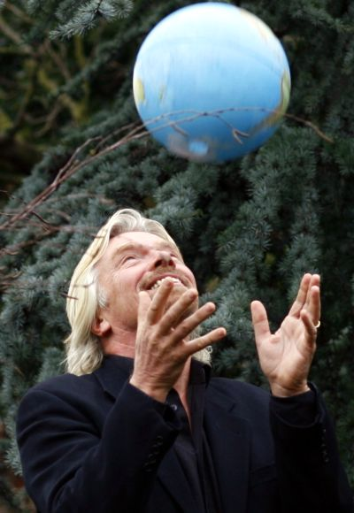 Airline tycoon Richard Branson throws a globe in the air.