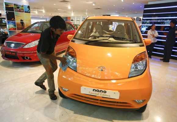 A showroom attendant cleans a Tata Nano car at their flagship showroom in Mumbai.
