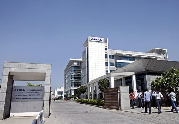 People walk in front of the HCL Technologies Ltd office at Noida.