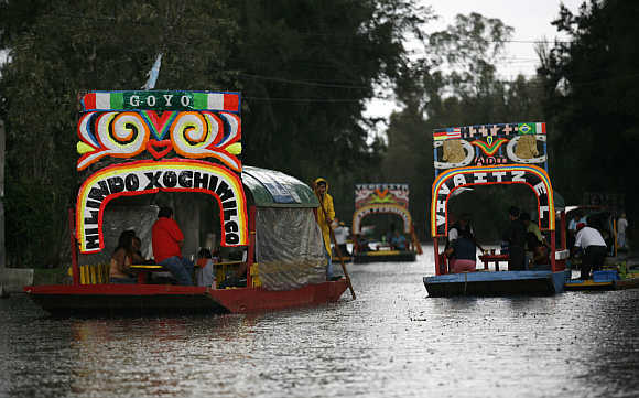 A man rows a Trajinera (boat) along the Xochimilco canals in Mexico City.