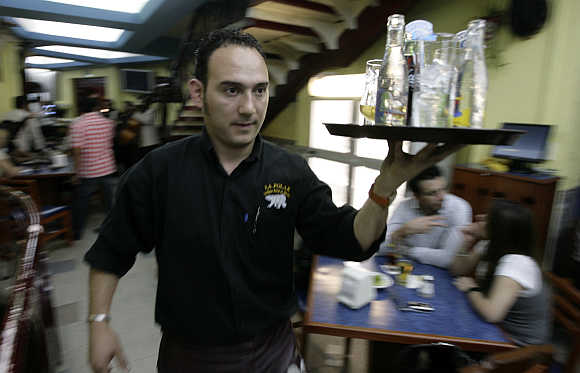 A waiter carries drinks in La Polar Bar in Mexico City.