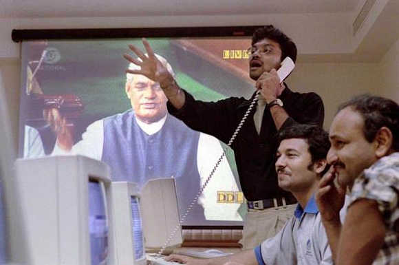 Stock brokers at a brokerage firm in Mumbai trade in front of a television screen displaying Atal Behari Vajpayee delivering his parliament address in New Delhi, April 17, 1999.