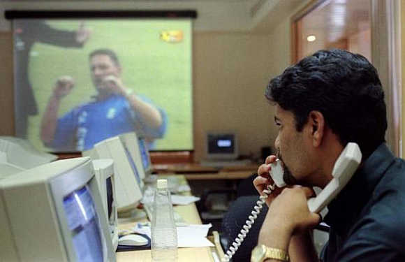A stock broker watches England play Sri Lanka in the inugural World Cup match as he trades on the phone in Mumbai, May 14.