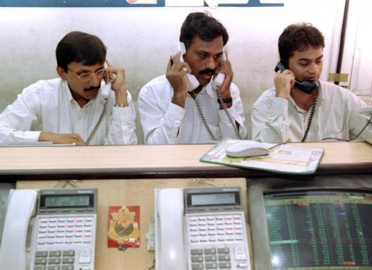 Stock brokers trade at a brokerage firm in Mumbai, July 12.