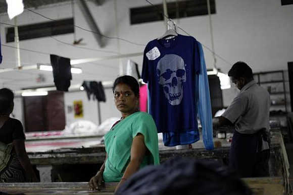 An employee stands next to a newly dyed T-shirt at the Estee garment factory in Tirupur, Tamil Nadu.
