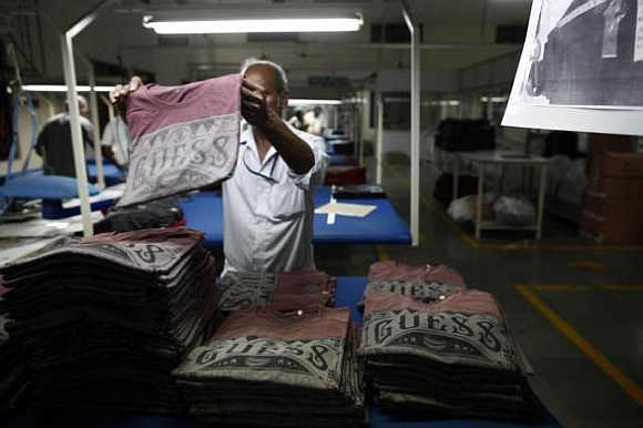 An employee sorts newly finished T-shirts at the Estee garment factory in Tirupur, Tamil Nadu.