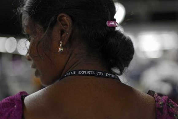 An employee wears a lanyard with the company's name printed on it as she works at the Estee garment factory in Tirupur, Tamil Nadu.