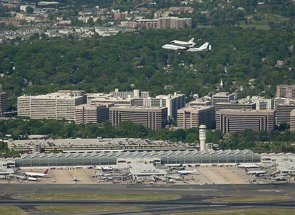 Space Shuttle Discovery, mounted atop a Nasa 747 Shuttle Carrier Aircraft , makes its way past Ronald Reagan Washington National Airport in Washington, DC.