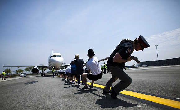 Members of the London Metropolitan Police Service tug an Airbus A320 jet for 100 feet during a race at John F Kennedy International Airport in New York.