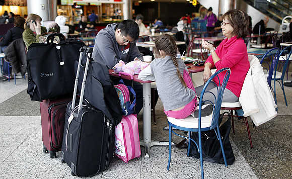 A family sits a table in the food court of LaGuardia Airport in New York.