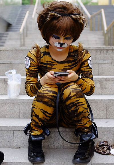 A volunteer wearing an animal costume checks her mobile phone as she waits t