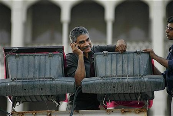 An electrician speaks on his mobile phone in Mumbai.