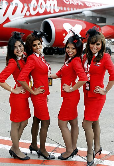 Stewardesses pose in front of an Airbus A340 passenger jet.