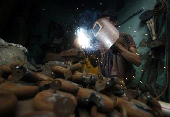An employee works inside a small-scale locks manufacturing factory at Aligarh district in Uttar Pradesh.