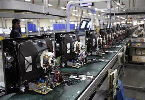 A worker at LG Electronics India Pvt Ltd. checks television sets on an assemble line inside a factory at Greater Noida in Uttar Pradesh.