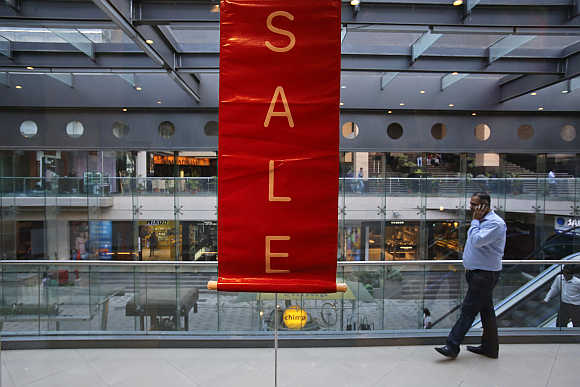 A man walks past a sale poster in a shopping mall in Mumbai.