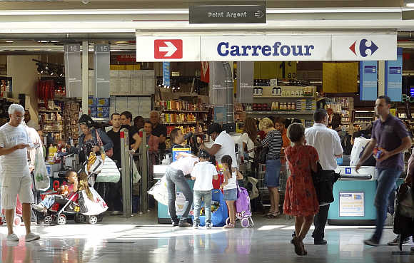 Customers queue at cash registers in a Carrefour supermarket in Montreuil near Paris.