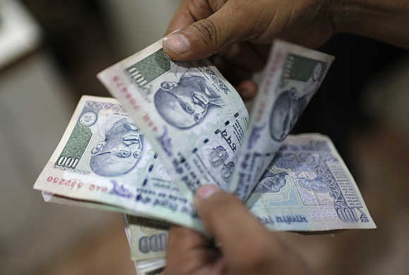 An employee counts rupee notes inside a private money exchange office in New Delhi.