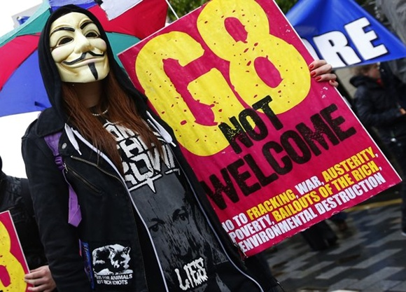A woman wearing a Guy Fawkes mask takes part in a demonstration in Belfast, against the upcoming G8 summit to be held near Enniskillen, June 15, 2013. Leaders of the G8 countries will meet at Lough Erne in Northern Ireland for the G8 Summit.