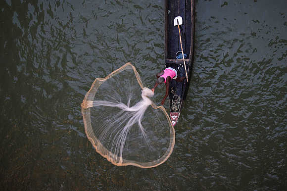 A fisherman casts his net into the Kathajodi River in Cuttack district, about 25km from Bhubaneswar.