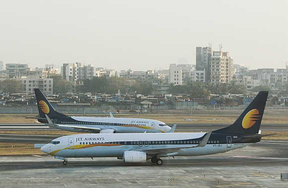 Jet Airways aircraft taxi on the tarmac at Mumbai airport.
