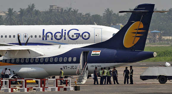 Staff stand next to parked passenger jets of IndiGo and Jet Airways (front) at Kolkata airport.