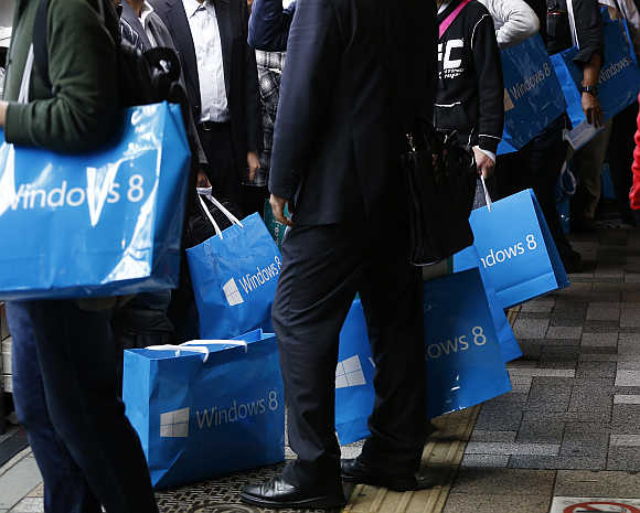 Customers wait to buy Microsoft's Windows 8 operating system outside an electronics store at the Akihabara district in Tokyo, Japan.