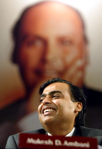 Mukesh Ambani, reacts with the image of his father and founder of the company Dhirubhai Ambani in the backdrop during the company's Annual General Meeting.