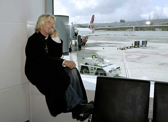 Richard Branson waits to board a flight aboard his airline in San Francisco, California.