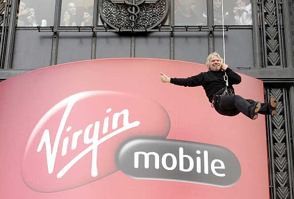 Richard Branson descends the facade of the Virgin Megastore building on Paris' Champs Elysees on a rope as he promotes his mobile phone service in France.
