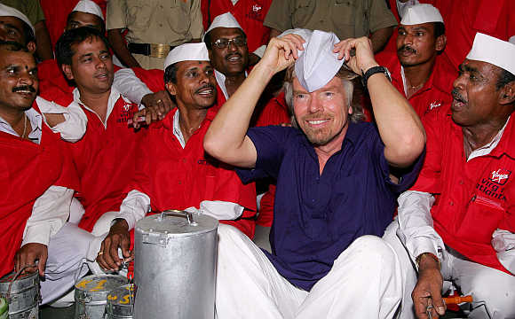 Richard Branson wears a cap as he sits amid lunch couriers, known as 'dabbawallas', at a railway station in Mumbai.