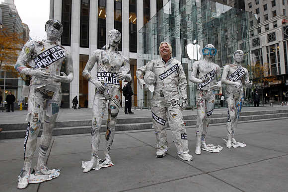Richard Branson, dressed in a newspaper suit, stands next to mannequins outside New York City's flagship Apple store.