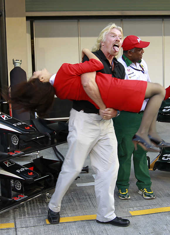 Richard Branson carries a stewardess before the qualifying session for the Abu Dhabi F1 Grand Prix at Yas Marina circuit in Abu Dhabi.